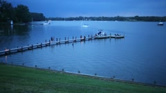 Wooden pier at scenic lake with boats and flashing in evening Stock Footage