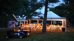 People rest during wedding under white tent. Small car is near tent Stock Footage