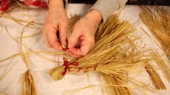 Female hands make straw folklore doll with red ropes on table - stock footage