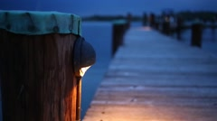 Wooden pole of pier at lake and legs of going man at night Stock Footage