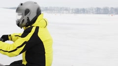 Man rides on skidoo on frozen river and people look at he Stock Footage