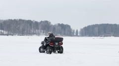 Man on quad bike rolls man on snowtube on frozen river at winter Stock Footage