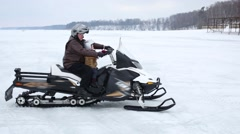 Father with son in helmets ride on skidoo on frozen river Stock Footage