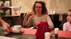 Mother and daughter sit in cafe and hands of waiter serve table Stock Footage