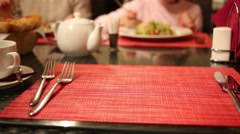 Woman with daughter eat out of focus and hands of waiter serve table Stock Footage