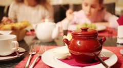 Woman with daughter eat out of focus and pot with dish is on table Stock Footage
