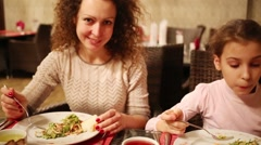 Curly woman with her daughter and eat salad in cafe - stock footage