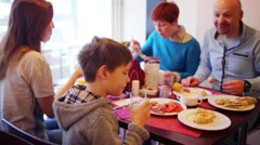 Father, mother and two children eat in small canteen Stock Footage