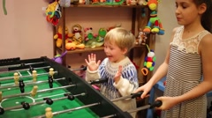 Girl with little boy play table soccer. Focus on boy Stock Footage