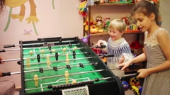 Happy mother and two children play table soccer in room Stock Footage