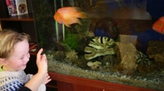 Happy cute little boy looks at fishes in aquarium in room Stock Footage