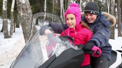 Sister and brother sit on snowmobile at winter day Stock Footage
