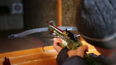 Boy teen takes aim and shoots crossbow in shooting gallery Stock Footage