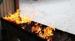 Charcoal fire for barbecue at winter, hand watering coal Stock Footage