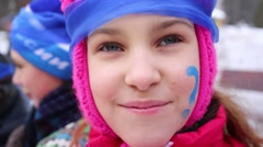 Pretty girl with painting face and blue headband smiles - stock footage