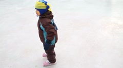 Little cute boy learns to skating at cold winter day on ice rink Stock Footage