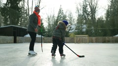 Happy mother and son play hockey at cold winter day on ice rink Stock Footage