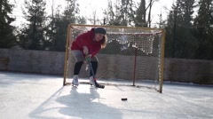 Happy young woman plays hockey as goalkeeper at winter on ice rink Stock Footage