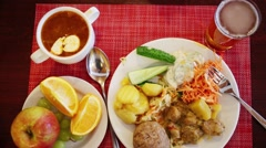 Cutlet, fried potatoes and salad on table and child hand takes fruit Stock Footage