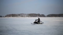 Man in helmet rides on snowmobiles on snowy field at winter Stock Footage