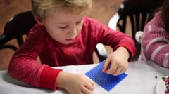 Close up portrait of little cute boy play mosaic at table Stock Footage