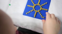 Close up of little cute girl playing mosaic - make yellow sun Stock Footage