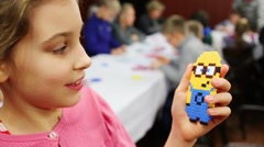 Girl holds Minion toy of mosaic - is figure from Despicable Me 2 Stock Footage