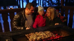 Father, mother and daughter make barbecue with meat at winter night Stock Footage