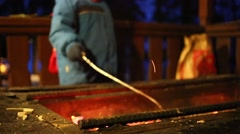 Child hands stir coals in brazier and bright sparks rise at night Stock Footage