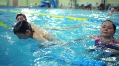 Two women and boy swim in indoor pool with floating dividers Stock Footage
