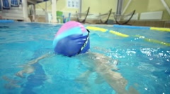 Little boy in goggles dives and touches bottom in pool Stock Footage