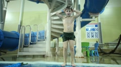 Little boy in shorts jumps into indoor pool and tumbles Stock Footage