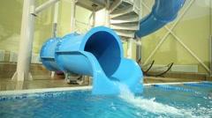 Two boys down on plastic water slide in big indoor pool Stock Footage