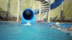 Boy teen down on plastic water slide in indoor pool. Stock Footage