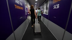 air passengers walk through a jet bridge to enter the arrival gate hall - stock footage
