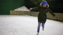 Pretty girl teen graceful skating on ice rink at winter night Stock Footage