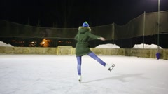 Girl teen graceful whirls on ice rink at winter night Stock Footage
