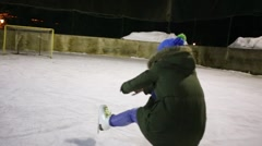 Girl teen skates as gun and falls on ice rink at winter night Stock Footage