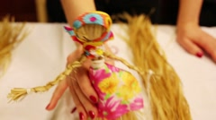 Female hands hold straw folklore doll in skirt on table Stock Footage