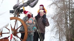 Mother, father and two kids play with steering wheel at winter Stock Footage