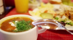 Dinner - soup in mug, meat with garnish, bread and fruits on table Stock Footage