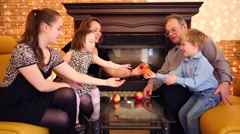 Mother, father and three childrens sit next to fireplace with fruits Stock Footage