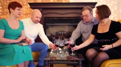 Four friends with red wine in glasses hobnob in room with fireplace Stock Footage