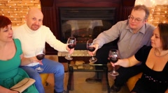 Four friends with red wine in glasses communicate in room Stock Footage