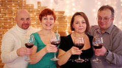 Four friends with red wine in glasses hobnob in room Stock Footage