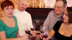 Four friends with red wine in glasses sit near fireplace and smile Stock Footage