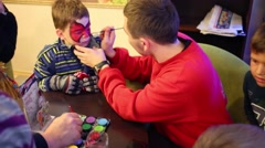 Man paints on face of child in Holiday House and Hotel Stock Footage