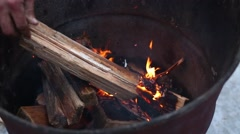 Flame in rusty metal tank and hand throwing log into fire Stock Footage