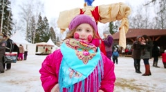 Little girl with painted face stands next to straw puppet and people Stock Footage