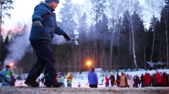 Boy go on log during holiday at winter and people out of focus Stock Footage